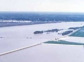 Floodwaters (right) overflow the flank of the Old River Control Structure (left foreground) during the flood of 1973.