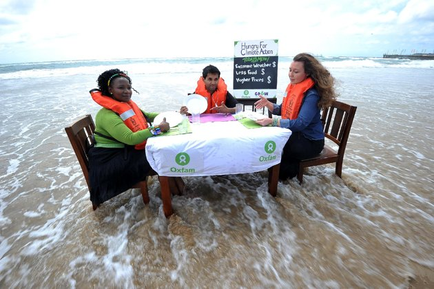 Oxfam volunteers demonstrate for non-readers the combined effects of rising seawater (climate change) and rising food prices. (AFP Photo/Alexander Joe)