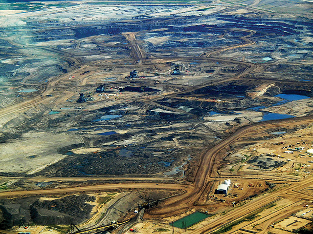 "Monster machines scrape tarry sand from the surface of Alberta, Canada. By applying enormous quantities of water and natural gas, they make a low quality, corrosive crude oil and proclaim a ""new Saudi Arabia."" (Photo by HowlMontreal/Flickr)"