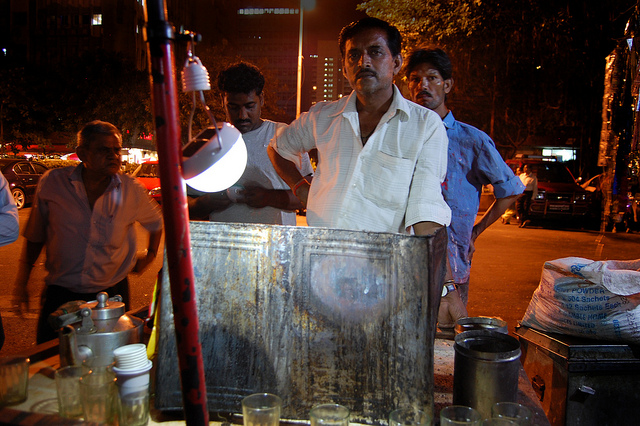 A Mumbai vendor uses a lamp, charged during the day by the solar panel he is holding, to bring business to his stall. Such affordable solar solutions are helping people all over the country deal with an unreliable (and seemingly unfixable) grid. (Photo by Nokero/Flickr)