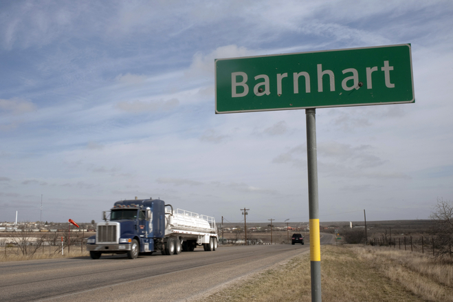 With thirsty oil rigs spearing the sky behind it, a water truck makes its run in Barnhart Texas,
